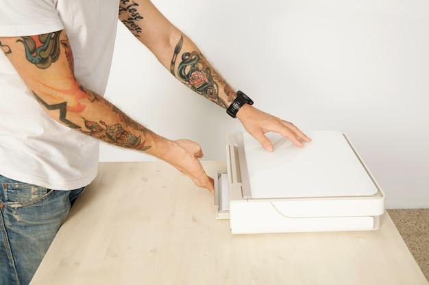 Tätowierter unerkennbarer mann schließt papierfach des hauptdruckerscanner-mehrfachgeräts, lokalisiert auf weiß Kostenlose Fotos
