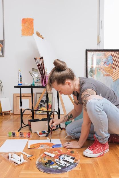 Tätowiertes junges weibliches künstlermalereibild, das auf boden sitzt Kostenlose Fotos
