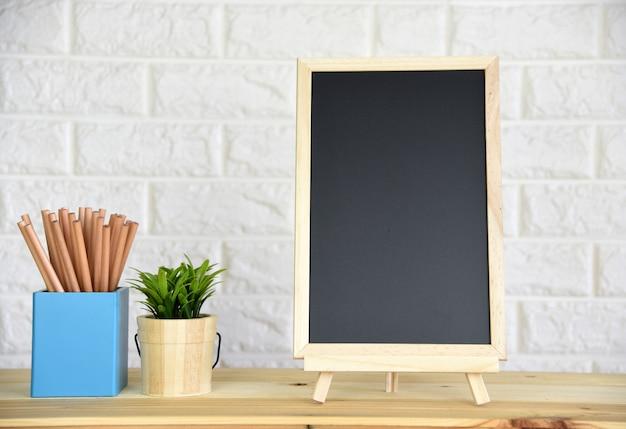 Tafel auf dem holztisch mit platz für ihren text. Premium Fotos
