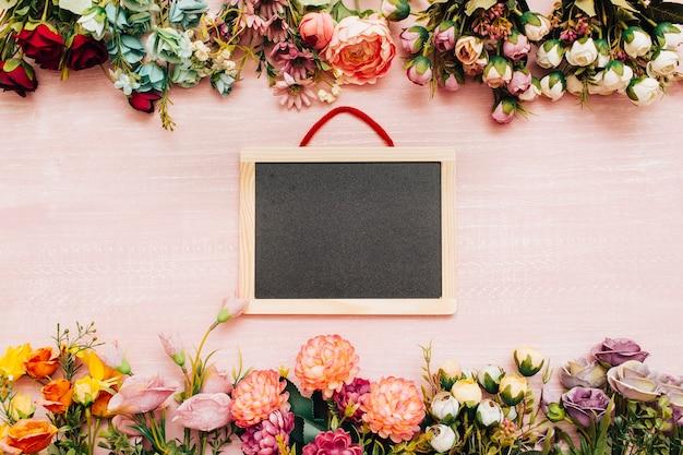 Tafel auf hölzernem hintergrund mit blumen Kostenlose Fotos