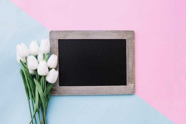 Tafel mit blumenstrauß von tulpen auf rosa und hellblauem hintergrund Kostenlose Fotos