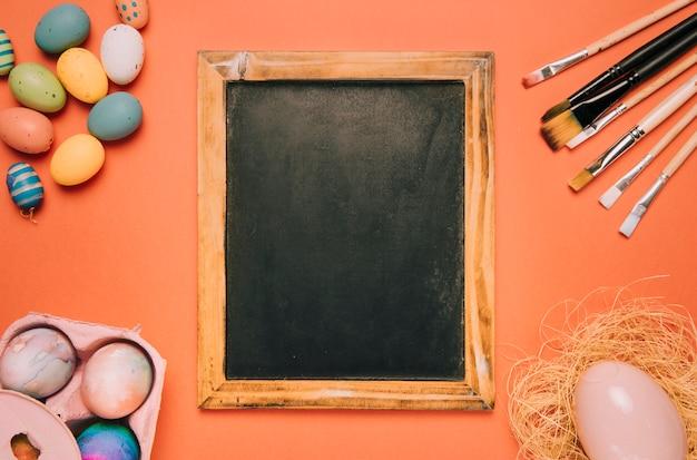 Tafel mit pinseln; ostereier auf einem orangefarbenen hintergrund Kostenlose Fotos
