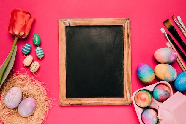 Tafel mit roter tulpe; ostereier und pinsel auf rosa hintergrund Kostenlose Fotos