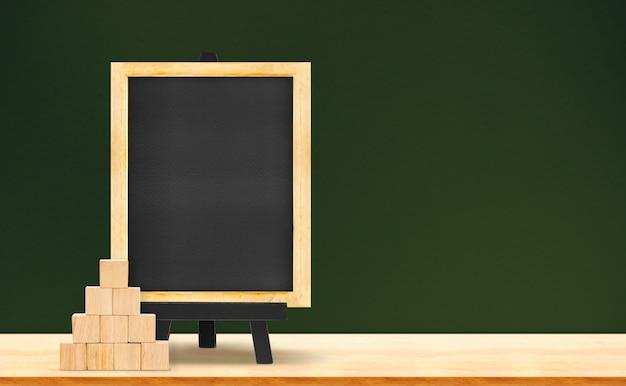 Tafel- und holzwürfel auf hölzerner tabelle auf dunkelgrünem hintergrund Premium Fotos