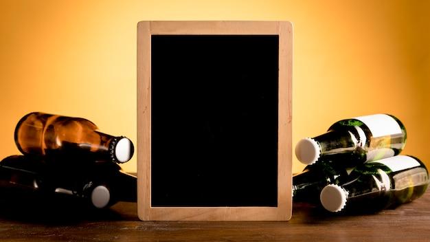 Tafel zwischen satz alkoholischen flaschen auf holztisch Kostenlose Fotos