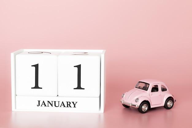 Tag 11 des januar-monats, kalender auf einem rosa hintergrund mit retro- auto. Premium Fotos