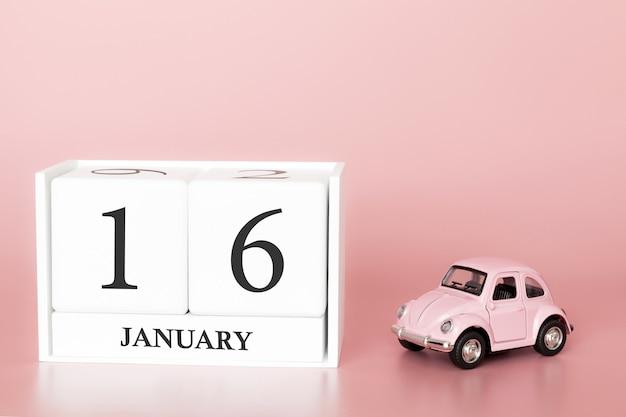 Tag 16 des januar-monats, kalender auf einem rosa hintergrund mit retro- auto. Premium Fotos
