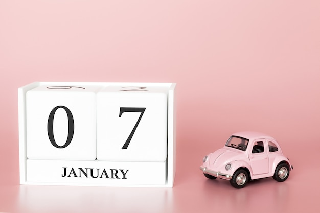 Tag 7 des januar-monats, kalender auf einem rosa hintergrund mit retro- auto. Premium Fotos