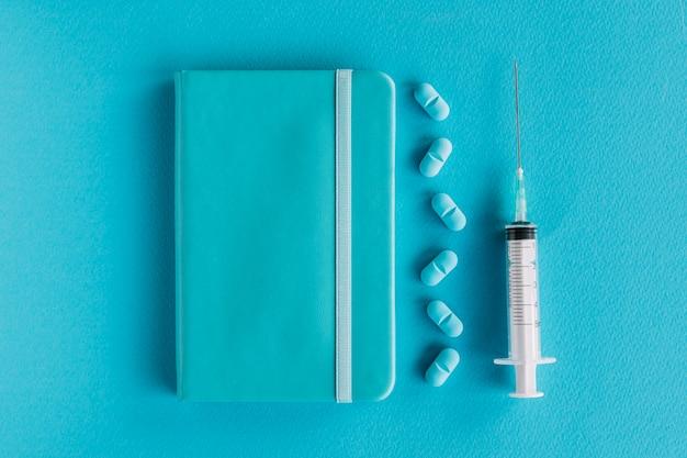 Tagebuch; pillen und spritze auf blauer oberfläche Kostenlose Fotos