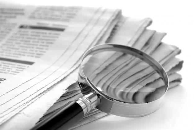 Tageszeitung und eine lupe, um nachrichten zu finden Premium Fotos
