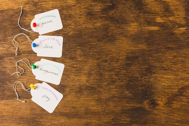 Tags mit handschriftlichen nachrichten, die durch push-pins auf einem hölzernen schreibtisch in reihe stecken Kostenlose Fotos