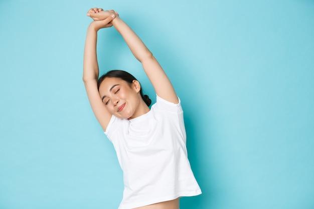 Taille des schönen asiatischen mädchens, das sich entspannt und glücklich fühlt, augen schließt und hände seitwärts streckt, sich energetisiert und optimistisch fühlt, bereit für neuen tag, stehenden blauen hintergrund. Premium Fotos