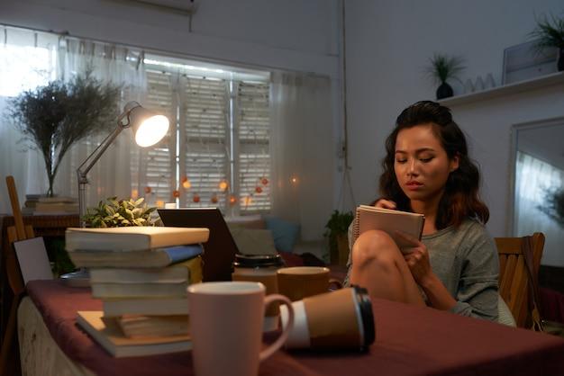 Taille herauf schuss des jungen mädchens sitzend an ihrem schreibtisch mit stapel des lehrbuchschreibens Kostenlose Fotos
