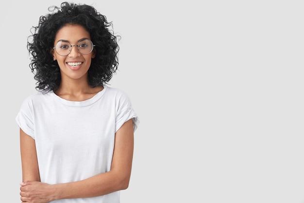Taille hoch porträt der glücklichen dunkelhäutigen frau mit afro-frisur, lächelt sanft Kostenlose Fotos