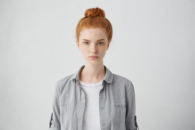 Taille hoch porträt der schönen europäischen 20-jährigen frau mit sommersprossen und haarknoten posiert isoliert Kostenlose Fotos