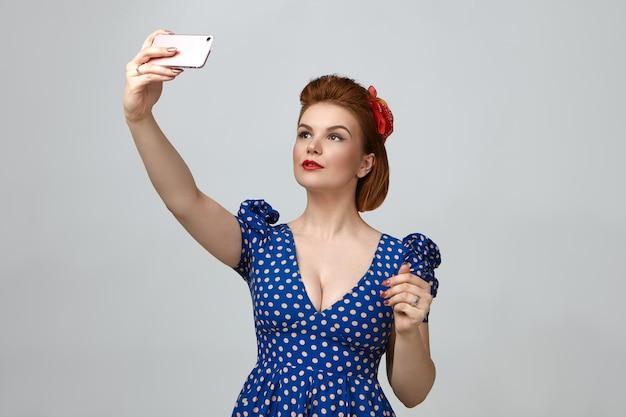 Taille hoch porträt der wunderschönen modischen jungen dame gekleidet wie 1950er jahre pin-up-mädchen hält smartphone über sich und nimmt selfie Kostenlose Fotos
