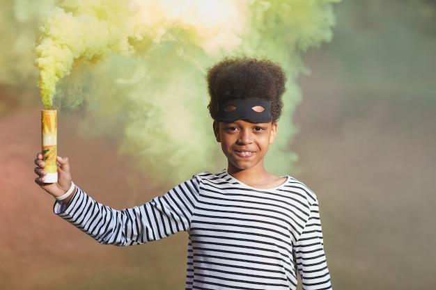 Taille hoch porträt des lächelnden afroamerikanischen jungen, der halloween-kostüm trägt und während grüner rauch hält, kopienraum Premium Fotos