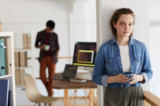 Taille hoch porträt des weiblichen it-programmierers, der kamera beim codieren des bechers mit computercode im hintergrund, kopierraum betrachtet Premium Fotos