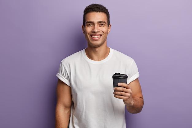 Taille hoch schuss von lächelnden fröhlichen gutaussehenden kerl hält papier zum mitnehmen kaffee, genießt freizeit mit freund, trinkt aromatisches getränk, trägt weißes modell t-shirt, modelle gegen lila wand Kostenlose Fotos