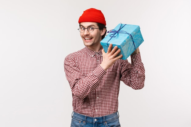 Taille-up-porträt glücklich und aufgeregt niedlichen bärtigen kerl versuchen zu raten, was in der box ist, schütteln verpacktes geschenk neugierig, was freund ihm für b-tag geben, lächelnd entzückt und fröhlich, stehen Premium Fotos