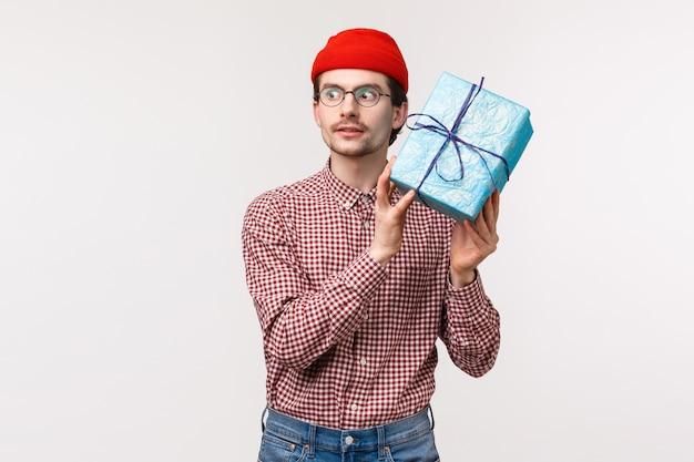 Taillenporträt aufgeregter kaukasischer bärtiger kerl in der roten mütze, schütteln der blau eingewickelten geschenkbox in der nähe des ohrs als versuch zu raten, was drinnen ist, schauen begeistert, unboxing-geschenk auf b-day-party-feier Premium Fotos