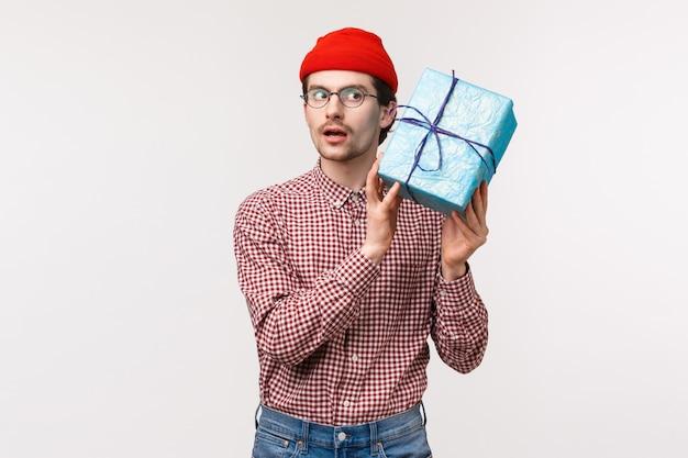 Taillenporträt des neugierigen lustigen kaukasischen bärtigen mannes in der roten mütze, in den gläsern, die geschenkbox nahe ohr schütteln, als erraten, was drinnen ist, schauen konzentriert, wollen überraschung öffnen und gegenwart sehen Premium Fotos