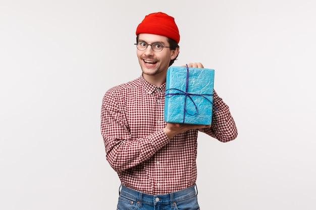 Taillenporträt freundlicher lustiger süßer mann kaufte geschenk für seinen kumpel, hielt verpacktes geschenk und lächelte, kaufte überraschungsgeschenk als zur b-tagesparty gehend, in der roten mütze Premium Fotos