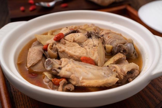 Taiwanesisches essen - hausgemachte köstliche sesamöl-hühnersuppe in einer schüssel auf dunklem holztischhintergrund. Premium Fotos