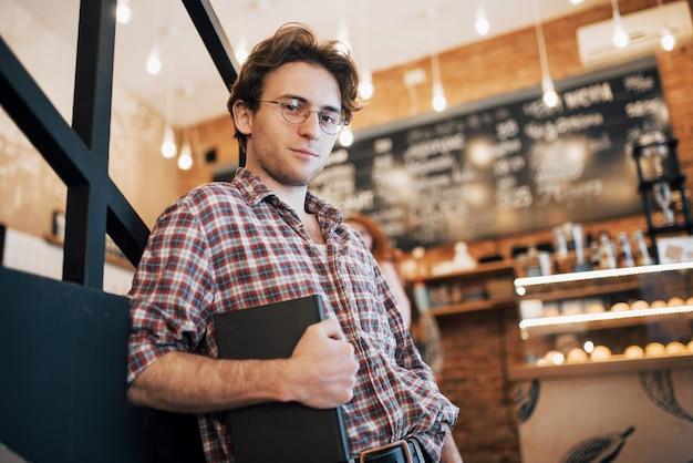 Talentierter junger mann im freizeithemd, der ein notizbuch in einem café hält. Kostenlose Fotos
