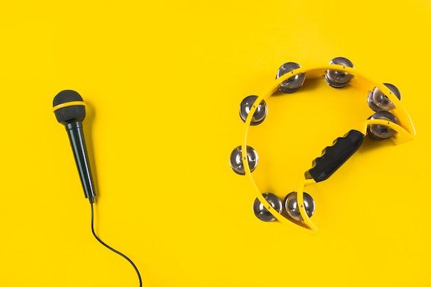 Tamburin mit mikrofon auf gelbem hintergrund Kostenlose Fotos