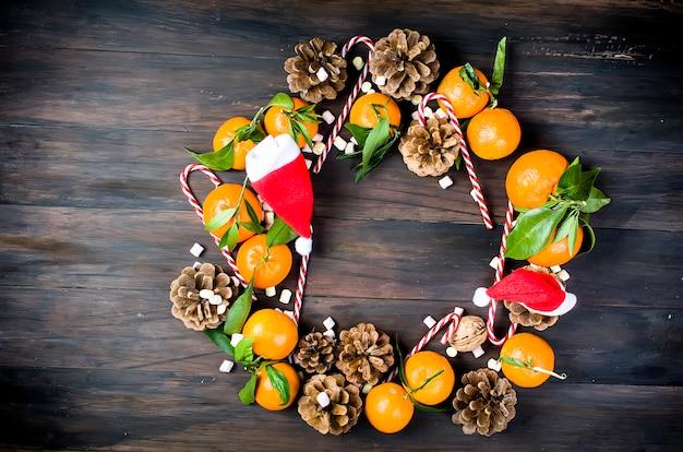 Tangerinenklementine mit blättern und weihnachtsspielwaren auf einem holztisch. Premium Fotos