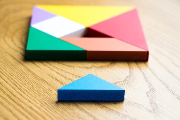 Tangram puzzle in quadratischer form, die auf holz hintergrund warten auf vollständigkeit Premium Fotos