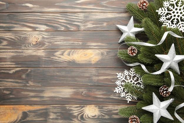Tannenbaumaste mit silberner weihnachtsdekoration auf einem braunen hintergrund Premium Fotos