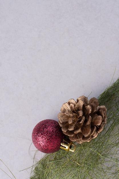 Tannenzapfen mit weihnachtskugel auf weißer oberfläche Kostenlose Fotos