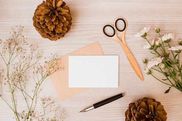 Tannenzapfen; schere; aster- und babyatmungsblumen; füllfederhalter und leere karte auf schreibtisch aus holz Kostenlose Fotos