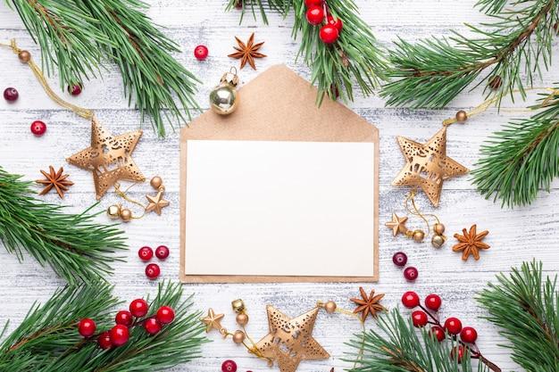 Tannenzweige, geschenke und ein umschlag auf einem hellen hölzernen hintergrund Premium Fotos