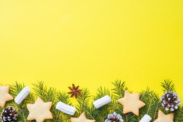 Tannenzweige, kekse und marshmallows auf gelb Premium Fotos
