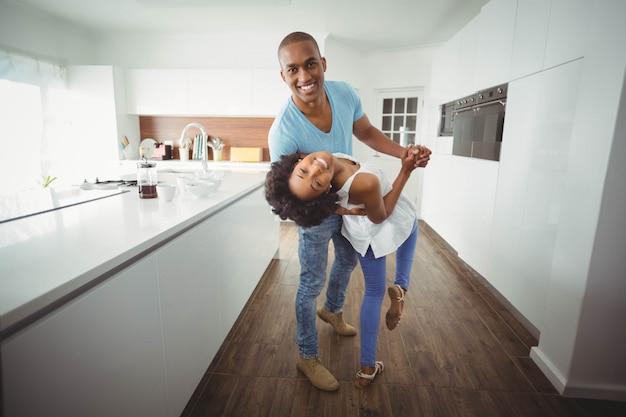 Tanzen des glücklichen paars in der küche und betrachten der kamera Premium Fotos