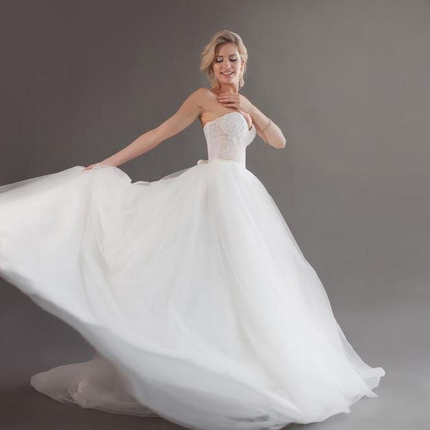 Tanzende junge braut im luxuriösen hochzeitskleid. hübsches mädchen in weiß. gefühle des glücks, des gelächters und des lächelns, grauer hintergrund Premium Fotos