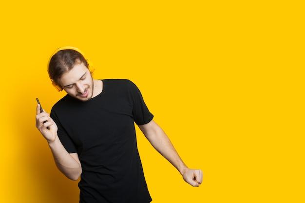 Tanzender kaukasischer mann mit langen haaren und bart, der musik unter verwendung von telefon und kopfhörern auf einer gelben wand mit freiem raum hört Premium Fotos