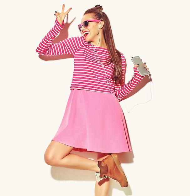 Tanzendes schönes glückliches nettes lächelndes sexy brunettefrauenmädchen in der zufälligen bunten rosa sommerkleidung Kostenlose Fotos