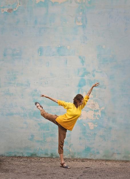 Tanzenhaltung einer frau in der gelben strickjacke Premium Fotos