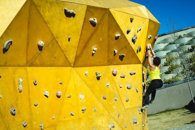 Tapfere frau, die ihre kletternden muskeln auf einem kletterwand in der sonne ausbildet. Premium Fotos