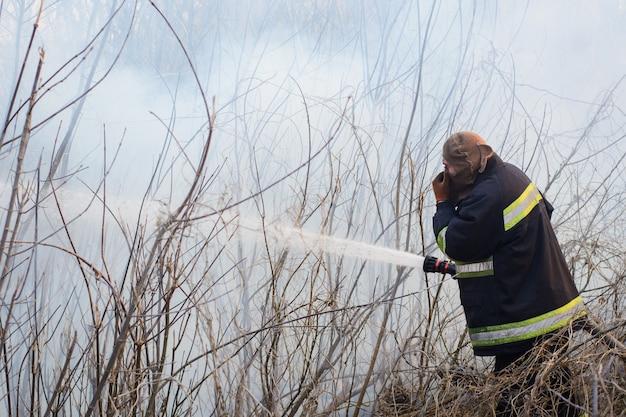 Tapferer feuerwehrmann steht im rauch, kämpft wildes feuer in der landschaft Premium Fotos
