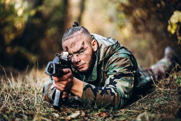 Tarnsoldat mit dem gewehr und gemaltem gesicht, die im gras liegt, das das gewehr anstrebt. Premium Fotos