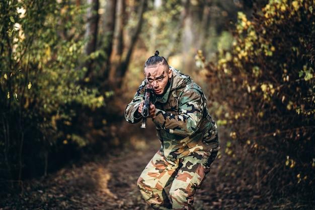 Tarnungssoldat mit dem gewehr und gemaltem gesicht, die draußen airsoft im wald spielen Premium Fotos