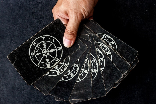 Tarockkarte für das wählen astrologisch in seiner hand auf schwarzem hintergrund Premium Fotos