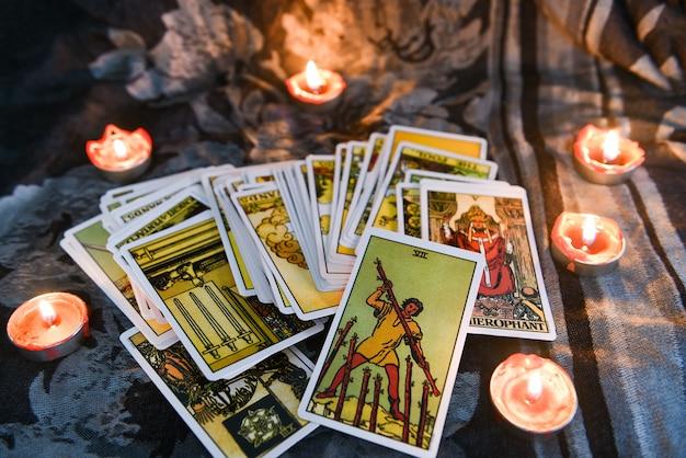 Tarotkarte mit kerzenlicht auf dem dunkelheitshintergrund für astrologie okkulte magische illustration - magische geistige horoskope und palme, die wahrsagerkonzept lesen Premium Fotos