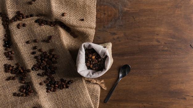 Tasche mit kaffee und löffel in der nähe von bohnen Kostenlose Fotos