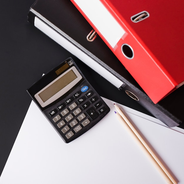 Taschenrechner; bleistifte; papier- und papierdateien auf schwarzem hintergrund Kostenlose Fotos